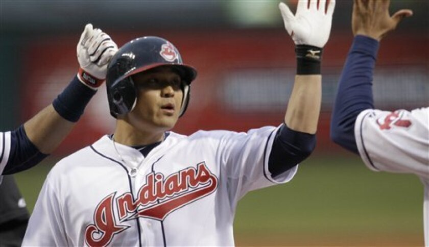 Cleveland Indians' Shin-Soo Choo is congratulated by teammates after hitting a two-run home run off Boston Red Sox's Daisuke Matsuzaka in the first inning of a baseball game Wednesday, April 6, 2011, in Cleveland. (AP Photo/Tony Dejak)