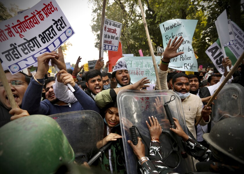 Security officers push back people shouting slogans during a protest held to show support to farmers who have been on a months-long protest, in New Delhi, India, Wednesday, Feb. 3, 2021. Nearly 200 supporters of Indian farmers on Wednesday clashed with the police who blocked them from marching to an area for protests close to Parliament in the Indian capital. Waving flags and banners representing their organizations, the protesters demanded the repeal of new agriculture reform laws which the farmers say will favor large corporate farms. (AP Photo/Manish Swarup)
