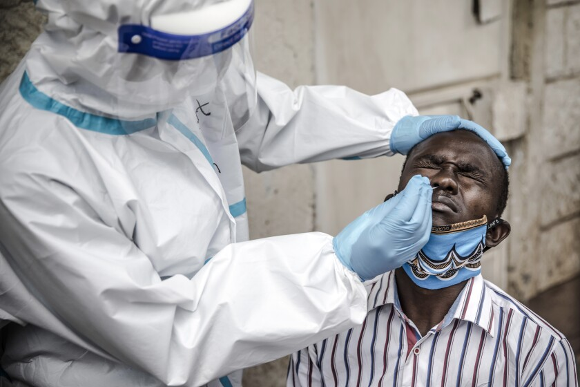 A Kenyan health worker uses a nasal swab to test a man for COVID-19 in the Kawangware slums of the capital, Nairobi.