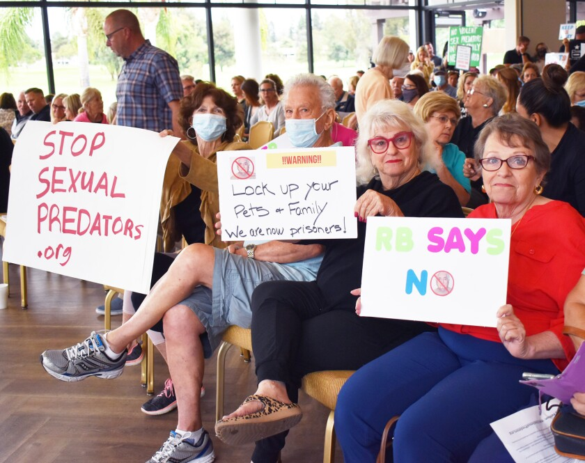 Rancho Bernardo residents held up signs to oppose sexually violent predator Douglas Badger's placement in their community.