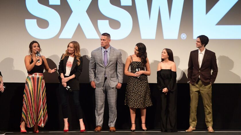 """Kay Cannon speaks at the SXSW """"Blockers"""" premiere at the Paramount in Austin, Texas, with, from left, Leslie Mann, John Cena, Geraldine Viswanathan, Gideon Adlon and Miles Robbins."""