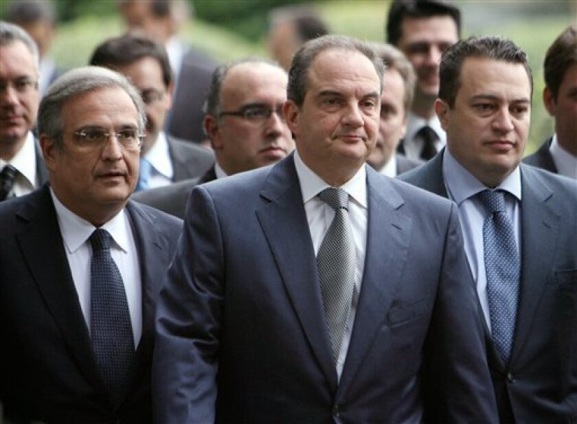 Greek Prime Minister Costas Karamanlis, front center, and new Finance Minister Yiannis Papathanasiou, left, and new Transport and Communications minister Evripidis Stylianidis, right, leave the Presidential Palace after the Cabinet swearing in ceremony in Athens on Thursday, Jan. 8, 2009.   Karaman