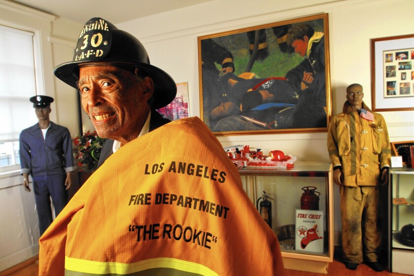 Retired Los Angeles city firefighter Arnett Hartsfield Jr. dons an original Bakelite helmet from Fire Station 30 on Central Avenue in downtown Los Angeles, where he began his LAFD career in 1940.