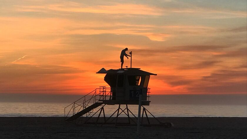 With the sunset behind him, Vitaliy Kostylov installs wireless communications technology and solar panels on a lifeguard tower at Huntington State Beach.