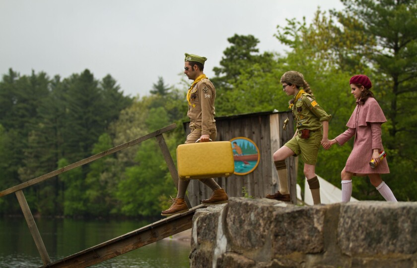 A scene from the movie Moonrise Kingdom of an adult and two young people about to cross a bridge