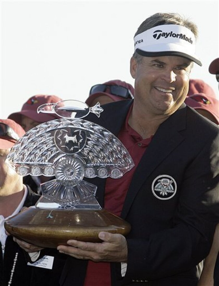 Kenny Perry lifts the winner's trophy after defeating Charley Hoffman on the third playoff hole to win the FBR Open golf tournament Sunday in Scottsdale, Ariz. (AP Photo/Paul Connors)
