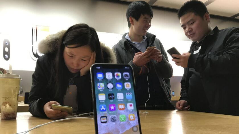 FILE - In this Nov. 6, 2017, file photo, shoppers check out the iPhone X at an Apple store in Beijin