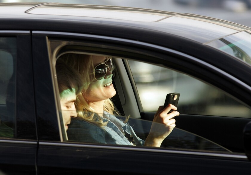 Una conductora parece estar enviando mensajes de texto, mientras maneja su auto en la intersección del bulevar Santa Mónica y Wilshire, en el Sur de California.
