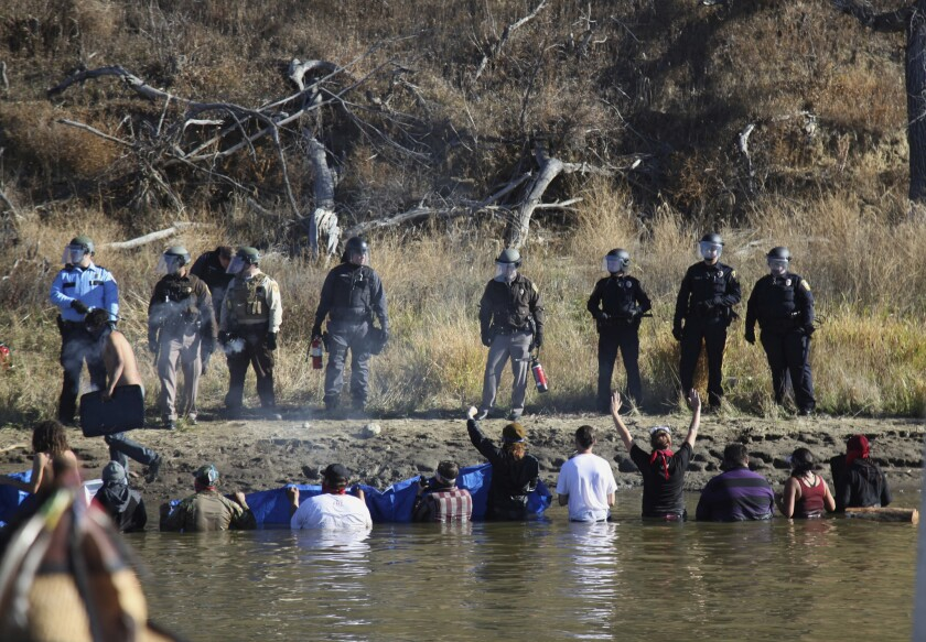 Dozens of protesters demonstrating against the expansion of the Dakota Access Pipeline wade in cold creek waters to confront local police.