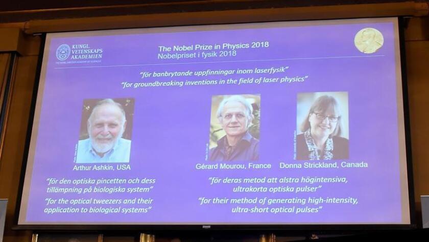 Los retratos de los tres ganadores del Nobel de Física, el estadounidense Arthur Ashkin (izq), el francés Gérard Mourou (c) y la canadiense Donna Strickland, son expuestos en la Real Academia de las Ciencias de Suecia, en la ciudad de Estocolmo, este 2 de octubre. EFE