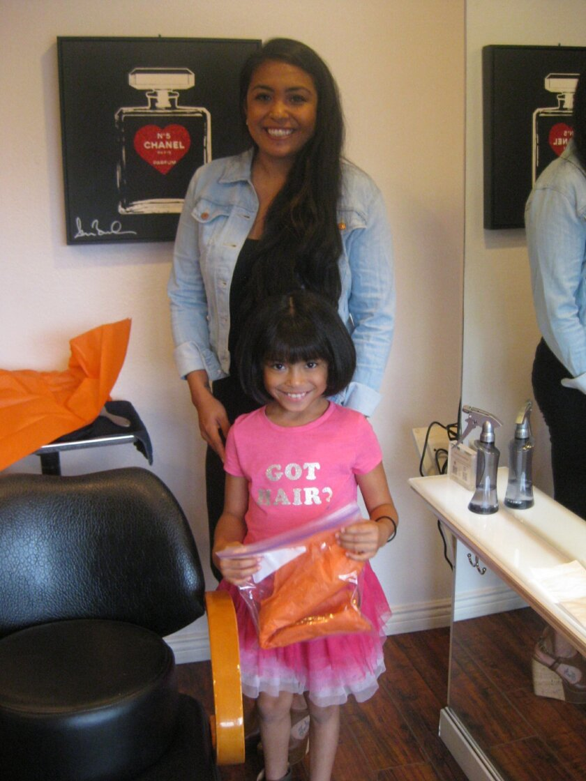 Gabriella 'Ella' Martinez with her mother, Erica, holds a bag containing 12 inches of hair Ella cut for charity at Salon Elle in La Jolla. Courtesy