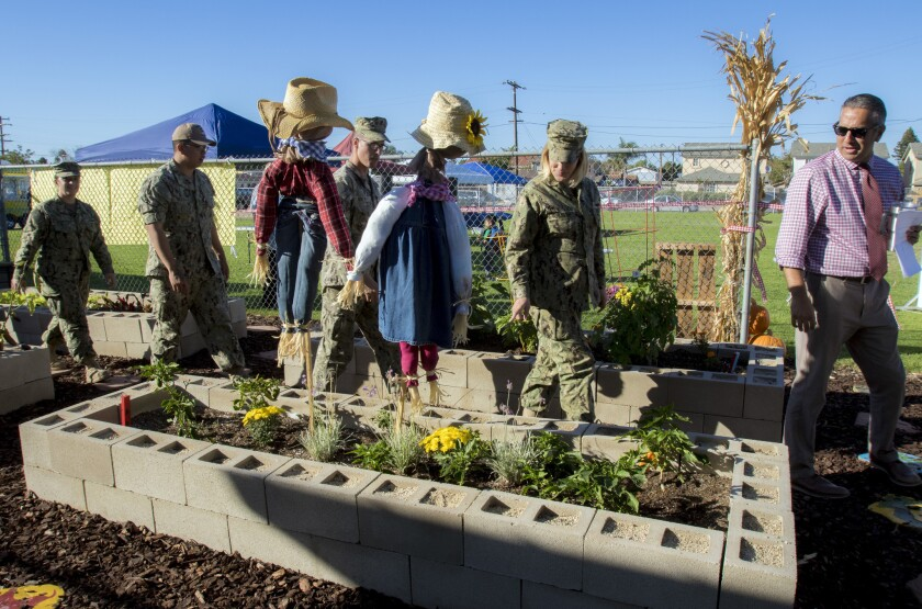 Principal Armando Lopez, right, leads Navy personnel through the school's new community garden prior to the dedication ceremony.