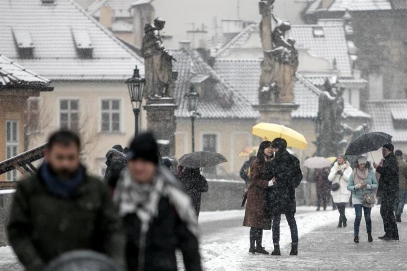 Varios turistas cruzan el puente Carlos durante una nevada en Praga (República Checa). EFE/Archivo