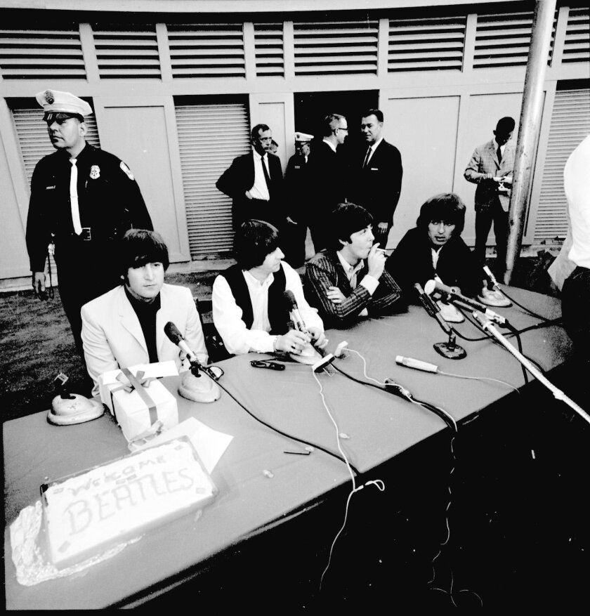 The Beatles are shown at a backstage press conference in 1965 at Balboa Stadium, prior to the iconic English rock band's only San Diego performance.