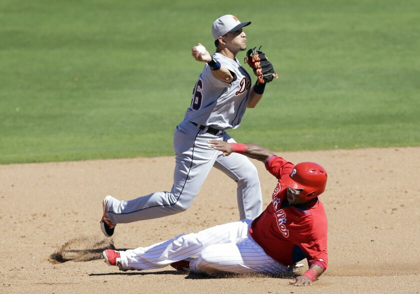 Philadelphia Phillies' Marlon Byrd slides safely under Detroit Tigers shortstop Hernan Perez, top, during a double play attempt in the third inning of an exhibition baseball game Friday, Feb. 28, 2014, in Clearwater, Fla. (AP Photo/Charlie Neibergall)