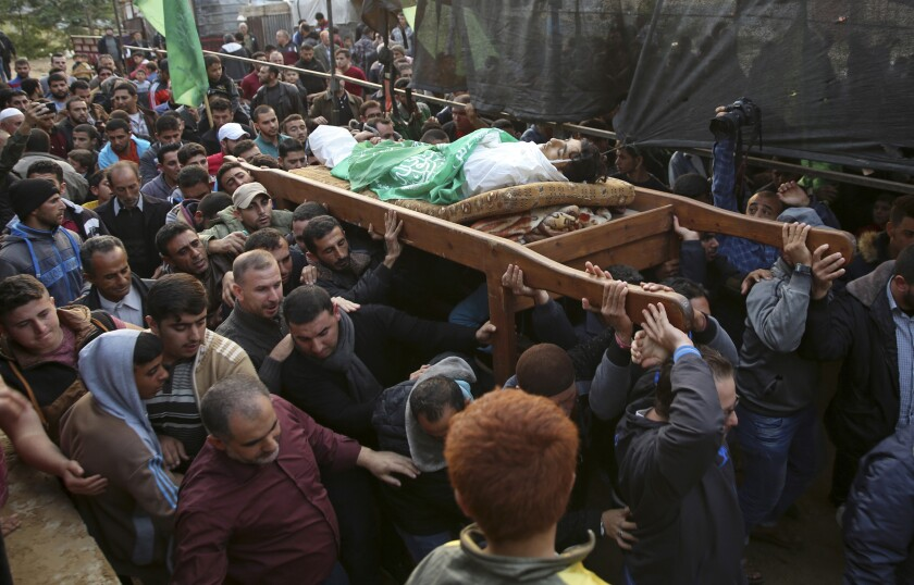 FILE - In this Nov. 15, 2018, file photo, mourners carry the body of Palestinian fisherman Nawaf Al-Attar, 20, who was shot and killed by Israeli troops on the beach near the border with Israel, during his funeral in Beit Lahiya, northern Gaza Strip. An Israeli soldier who shot and killed the Palestinian fisherman near the Gaza frontier in 2018 has been given 45 days of community service after an army investigation concluded he fired without authorization, the military said Thursday, June 18, 2020.(AP Photo/Adel Hana, File)