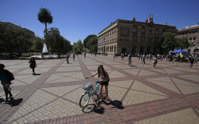 Students walking and on bikes roam the USC campus in 2014