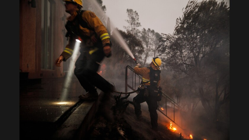 Contra Costa firefighters work to put out flames burning inside a home along Highway 29 north of Calistoga on Oct. 12.