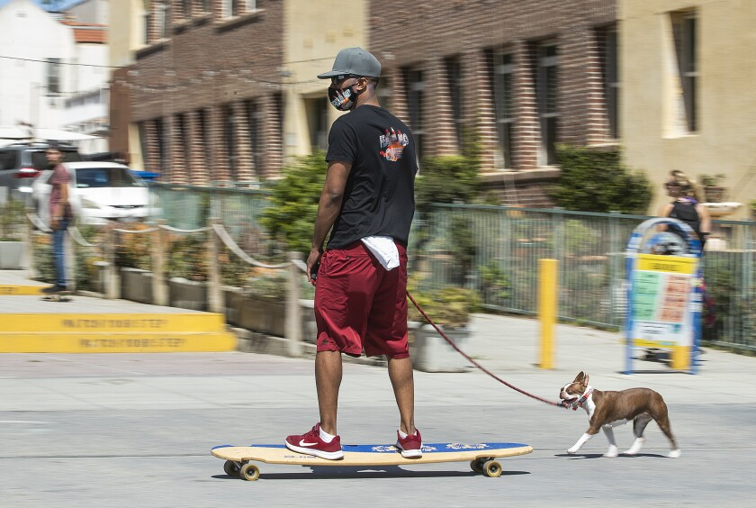A man on a skateboard leads his leashed Boston terrier on the Venice boardwalk