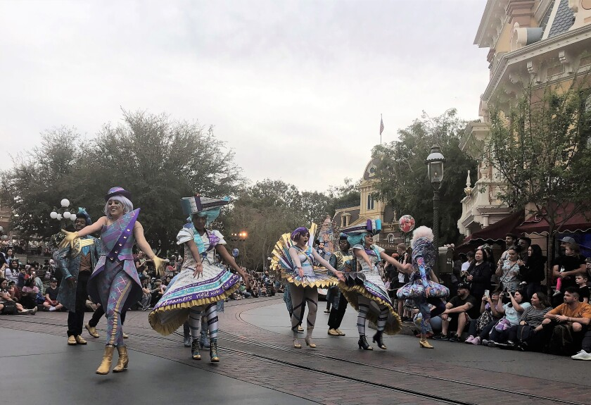 Costumed dancers interact with park-goers in the premiere of the Magic Happens parade at Disneyland Park on Feb. 28.