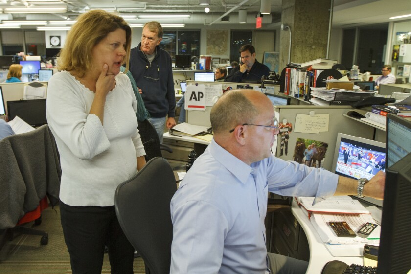 """Then-Associated Press Washington bureau chief Sally Buzbee, talks with Stephen Ohlemacher, who in 2020 is the decision desk editor, in the early morning hours of Wednesday, Nov. 9, 2016, at the Washington bureau of The Associated Press during election night. The Associated Press, one of several news organizations whose declarations of winners drive election coverage, is pulling back the curtain in 2020 to explain how it is reaching those conclusions. """"The general public has a more intense desire to understand it at a nitty-gritty level,"""" said Buzbee, who is now senior vice president and executive editor. (AP Photo/Jon Elswick)"""