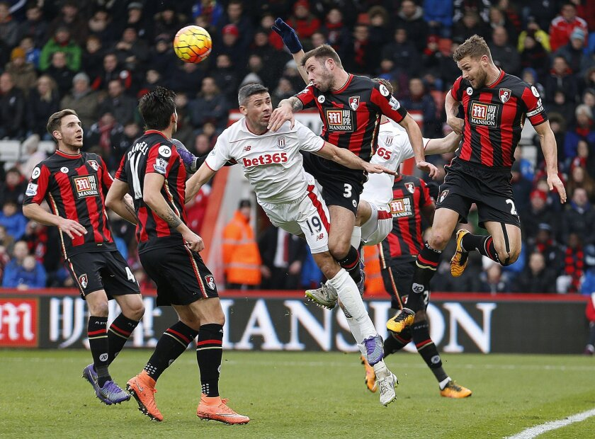 AFC Bournemouth's Simon Francis, right, and Steve Cook, second right battle for the ball with Stoke City's Jonathan Walters during the English Premier League soccer match at the Vitality Stadium, Bournemouth, England, Saturday Feb. 13, 2016. (Steve Paston/PA via AP) UNITED KINGDOM OUT