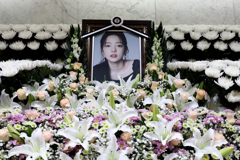 A memorial altar, surrounded by flowers, with a framed photo of K-pop star Goo Hara.