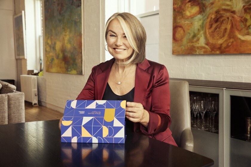 A woman sits at a dining table and smiles while holding up a box