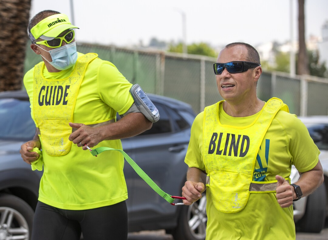 Tony Duenas, 53, right, a marathon runner who is blind, and his guide Ray Alcanter, demonstrate the technique they use