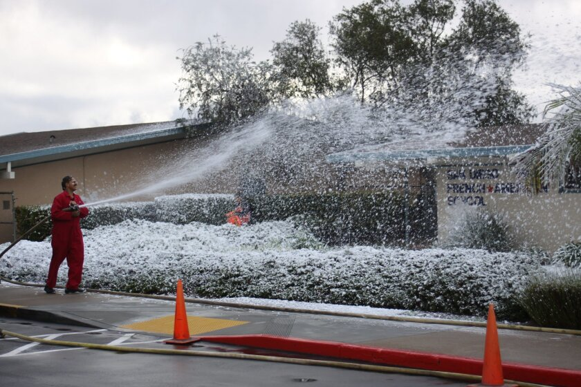 Raje Graham with Dr. Bronner's Magic Interblastic Foam Experience sprays faux snow along the front of the San Diego French-American School.