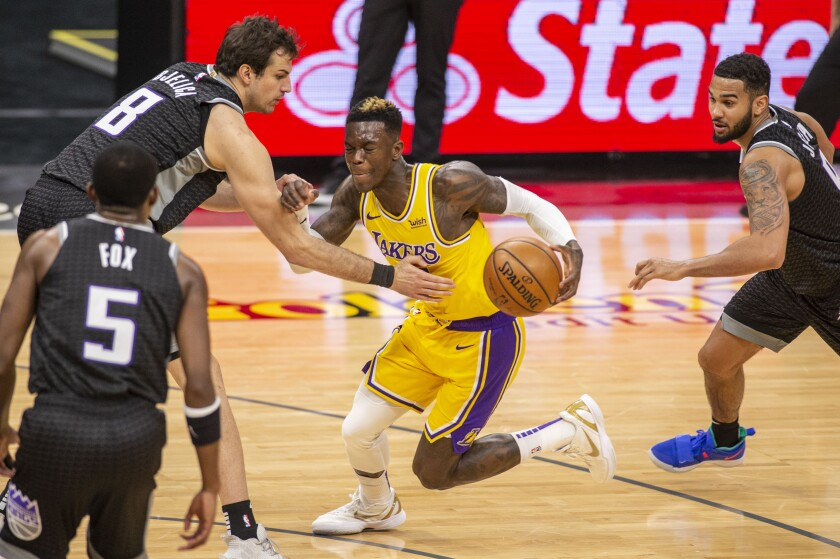 Lakers guard Dennis Schroder drives to the basket in front of Sacramento Kings forward Nemanja Bjelica.