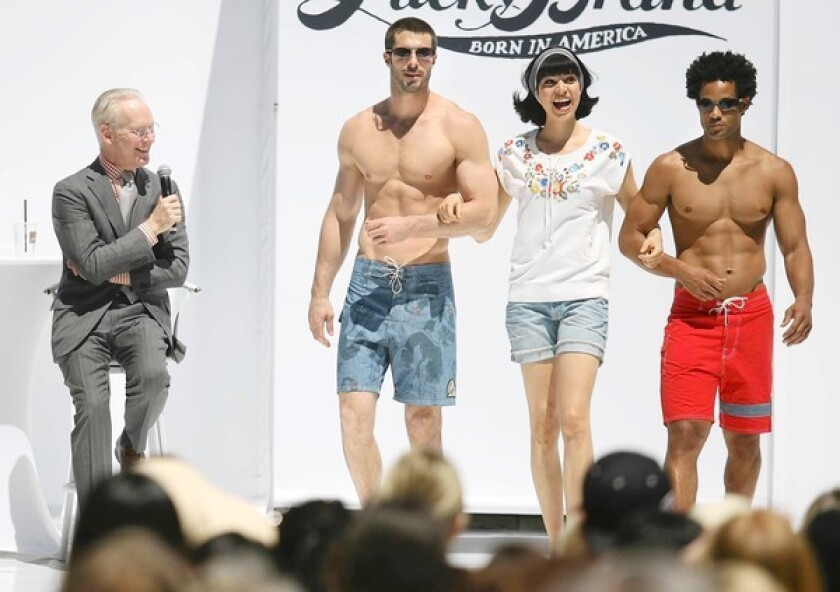 """Tim Gunn, left, chief creative officer at Liz Claiborne and co-host of the television show """"Project Runway,"""" watches as models strut down the runway during the Tim Gunn Fashion Presentation at Fashion Island on Saturday."""