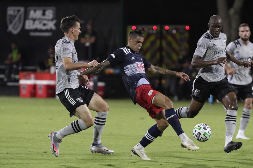 New England Revolution forward Gustavo Bou, center, attempts a shot against Montreal Impact defender Jukka Raitala, left, and defender Rod Fanni, right, during the first half of an MLS soccer match, Thursday, July 9, 2020, in Kissimmee, Fla. (AP Photo/John Raoux)