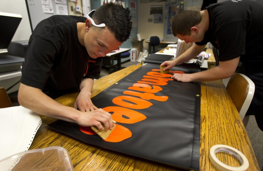 Rafael Maldonado (left) and Jordan Sams, students in the Virtual Enterprise class at Escondido High School, prepare a vinyl banner to be used in for the student-run Cougar Market, a farmers market held on campus.