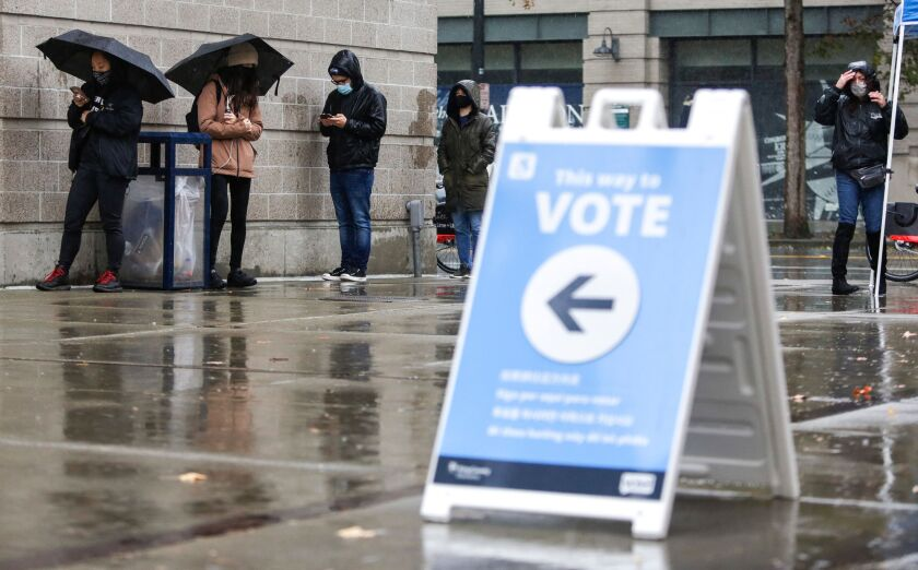 People line up in the rain on Election Day at a voting center set up at the CenturyLink Field Event Center.