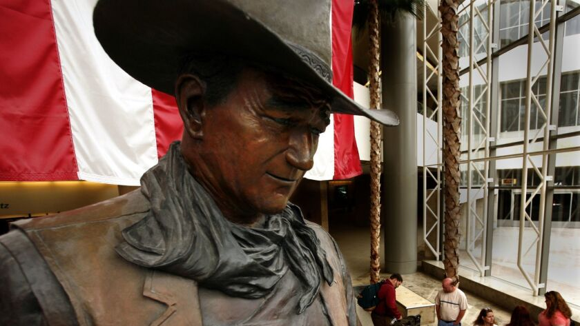 A bronze statue of John Wayne in a western hat and scarf
