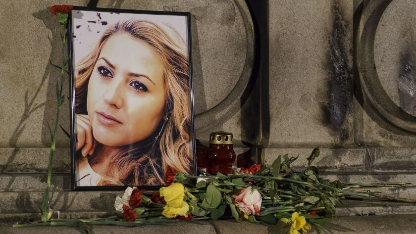 A portrait of slain television reporter Viktoria Marinova is placed on the Liberty Monument next to