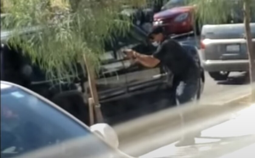 A still from witness video provided by SDPD shows a man pointing a weapon at officers just before they fatally shoot him.