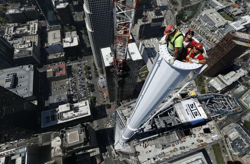 Iron workers are inside a spire attached to the Wilshire Grand Center in downtown Los Angeles. The InterContinental Los Angeles hotel will be part of the center.