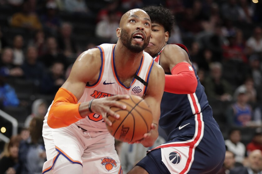 New York Knicks' Taj Gibson, front, moves past Washington Wizards' Rui Hachimura during the first half of an NBA basketball game Tuesday, March 10, 2020, in Washington. (AP Photo/Luis M. Alvarez)