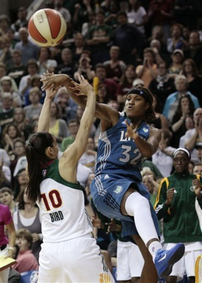 Minnesota Lynx's Rebekkah Brunson (32) passes as Seattle Storm's Sue Bird defends in the second half of a WNBA basketball game Thursday, June 9, 2011, in Seattle. The Lynx won 81-74. (AP Photo/Elaine Thompson)