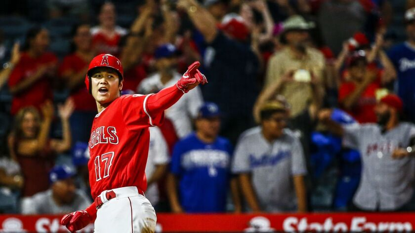 Angels designated hitter Shohei Ohtani (17) gestures after scoring to tie the game late in the ninth inning against the Los Angeles Dodgers.