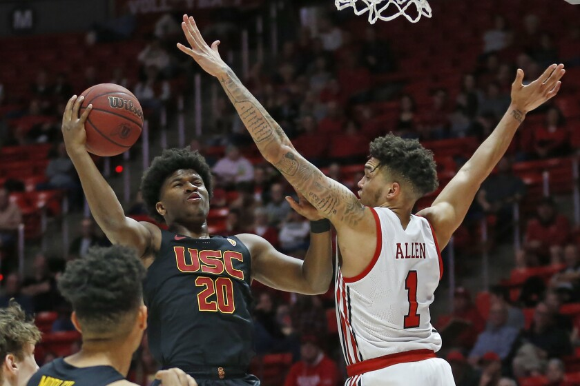 USC guard Ethan Anderson puts up a shot in front of Utah forward Timmy Allen during the first half of the Trojans' loss Sunday.