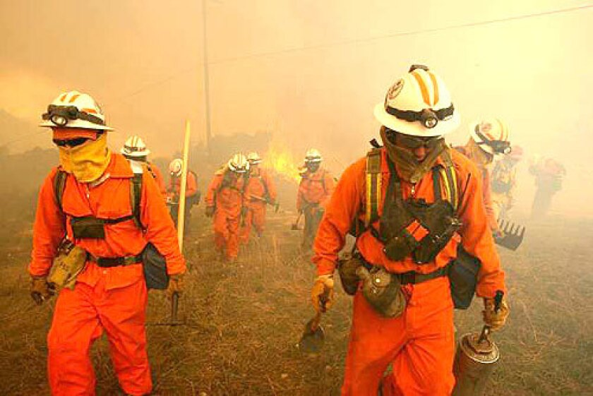 ON THE LINE: Inmate crews with the California Department of Corrections help fight the wind-whipped blaze that has blackened more than 6,500 acres in eastern Orange County. Nearby residents have been allowed to return home, but a major toll road remains closed.