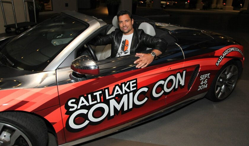 """Arrow"" cast member Manu Bennett poses for a photo in the Audi R8 Spyder while at the San Diego Comic-Con convention."