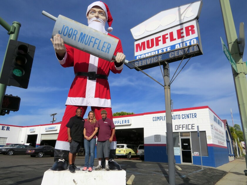 Joor Muffler owner Nick Manning, left, and Sickel's Fabrics co-owners Michelle Guillen and Felix Guillen pose with Escondido's muffler man statue, which is decked out once again in a Santa suit for the first time in a decade.