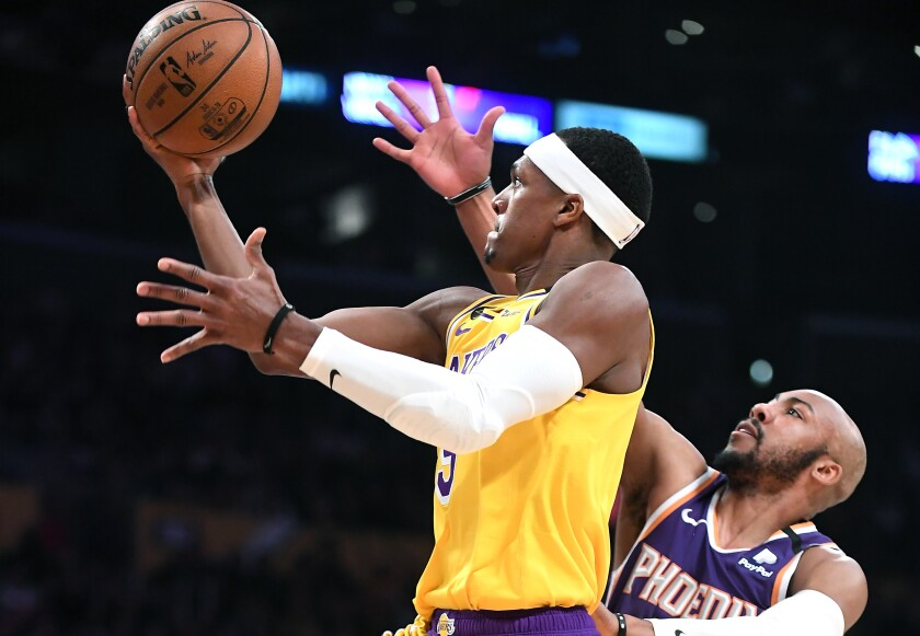 The Lakers' Rajon Rondo beats the Suns' Jevon Carter to score a basket in the third quarter at Staples Center on Monday.