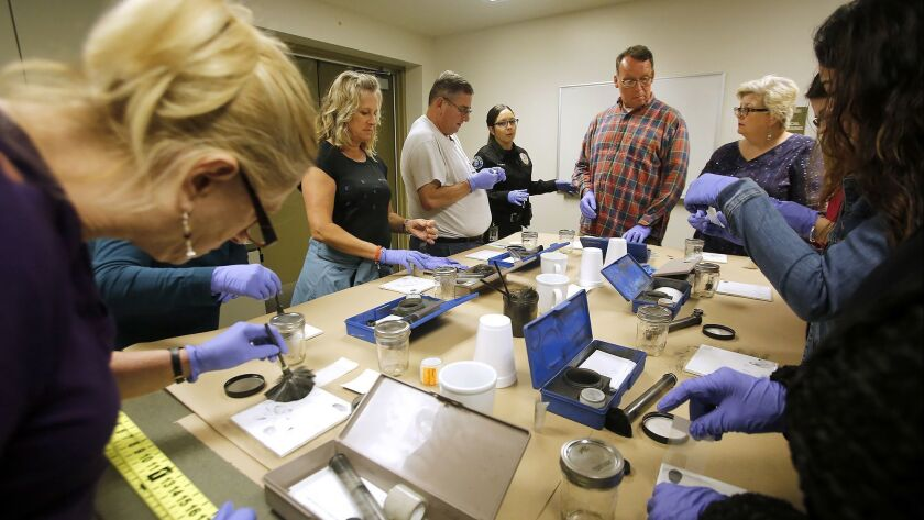 Instructor Krystal Aleman, center, shows how to reveal and collect fingerprint evidence from a crime
