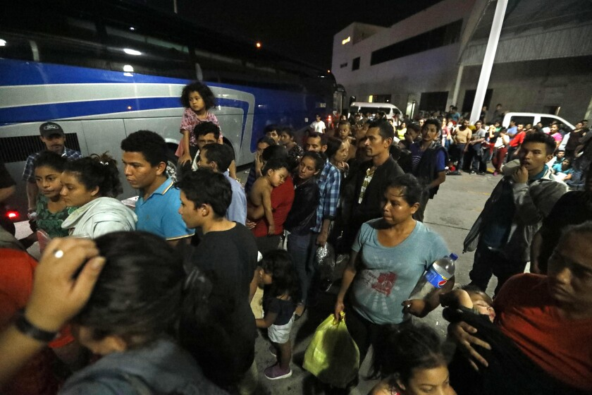NUEVO LAREDO, MEXICO, CA - AUGUST 2, 2019 - - Honduran asylum seekers line up to board one of four Chiapas-bound buses in a parking lot at an immigration check-point in Nuevo Laredo, Mexico on August 2, 2019. When the buses finally arrived in Nuevo Laredo at about 1 a.m. Friday, nearly 200 migrants rushed to line up. Many were smiling, relieved. One woman exclaimed: ÒThank God we can go!Ó Migrants were released into cartel-weary Nuevo Laredo this week stayed and slept in the parking lot of the immigration check-point for days struggling to find food, water and other necessities. Many headed back to their home country. (Genaro Molina / Los Angeles Times)