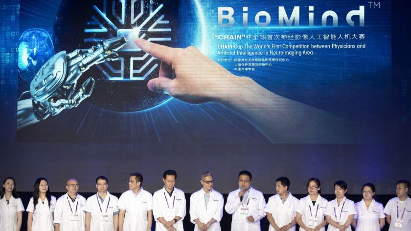 """A team of doctors line up before the start of the competition pitting physicians against a robotic """"doctor"""" at the China National Convention Center in Beijing on June 30, 2018."""